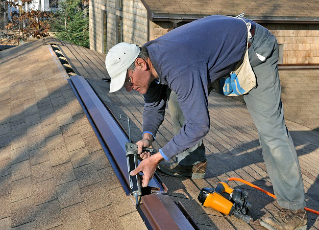 roofing contractor installing roof ridge vent on brown roof