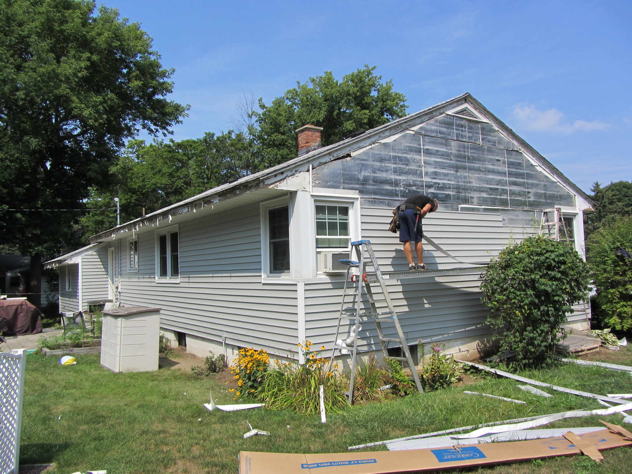 siding contractor installing vinyl siding on ranch house