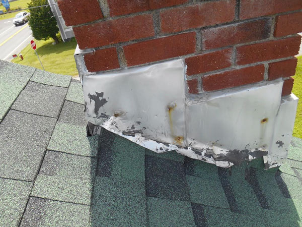 roof shingles with old flashing next to chimney